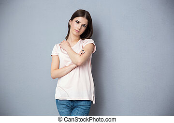 Portrait of a beautiful young woman standing over gray background