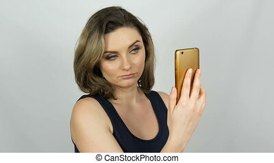 Portrait of a beautiful young woman who is posing making a selfie and communicating and looking into a smartphone that is holding in her hands on white background in studio