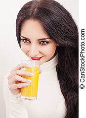 Portrait of a beautiful young woman with a glass of juice and orange, on white background
