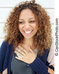 Portrait of a beautiful young woman with curly hair laughing