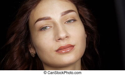 Portrait of a beautiful young woman with permanent lip makeup and microblading eyebrow tattoo posing in front of the camera in the studio.