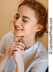 portrait of a beautiful young woman with red hair, smiling with happiness