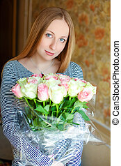 Portrait of a beautiful young woman with a bouquet of red roses