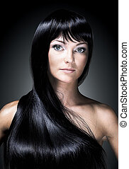 Portrait of a beautiful young woman with elegant long shiny hair. Isolated on black background