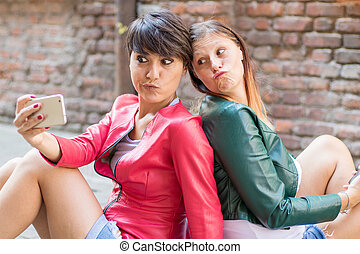Portrait of a beautiful young women doing selfie in the city with a smartphone