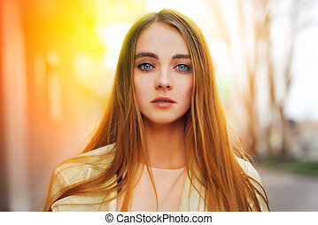 Portrait of a beauty blond woman at the sunny street