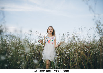 Portrait of a beauty blonde girl with blue eyes and long hair on her head walking in field with white flowers