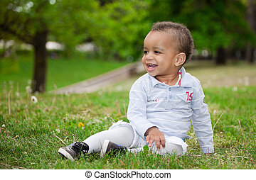 Portrait of a black baby boy playing  in the park