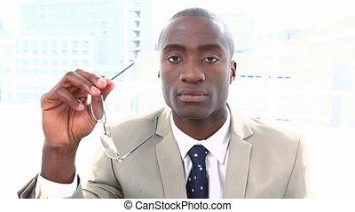 Portrait of a black businessman holding glasses