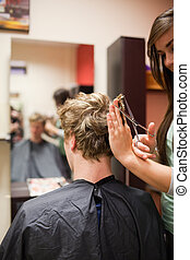 Portrait of a blond-haired man having a haircut