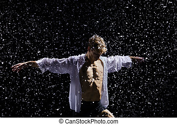 Portrait of a blond man in a white unbuttoned shirt posing in a dark studio against the backdrop of snowfall and studio light. Close up.
