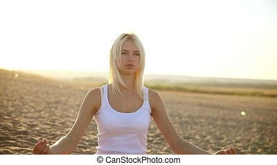 Portrait of a blond woman dressed in white sitting on the sand in the desert meditating yoga healthy lifestyle