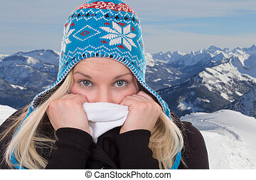 Portrait of a blond woman in winter cold in mountains