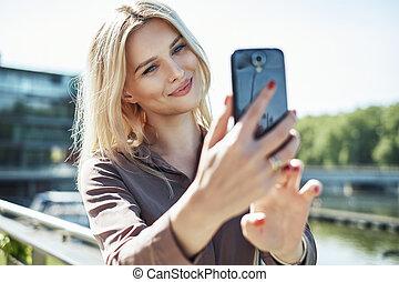 Portrait of a blond woman taking a selfie