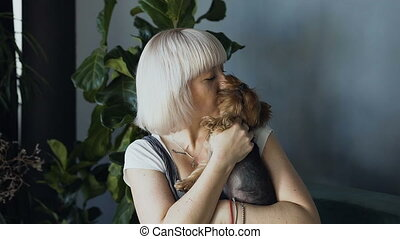 Portrait of a blonde girl kissing and hugging her little dog against a background of gray wall.