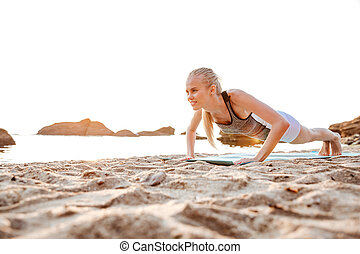 Portrait of a blonde woman doing planking on yoga mat