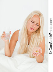 Portrait of a blonde woman looking at a pill with the camera...