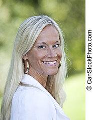 Portrait of a blonde woman smiling.