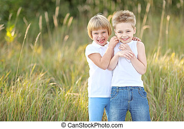 Portrait of a boy and girl on the meadow in summer