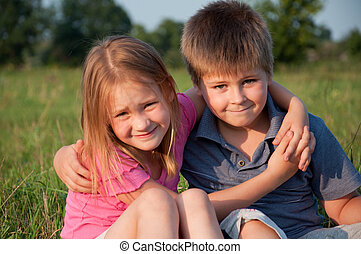 Portrait of a boy and girl outdoors in summer
