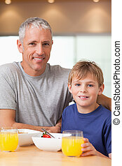 Portrait of a boy and his father having breakfast