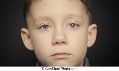 Portrait of a boy close-up on a black background