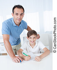 Portrait Of A Boy Doing Homework With His Father