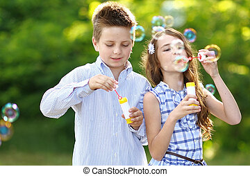 Portrait of a boy girl in a summer with bubble
