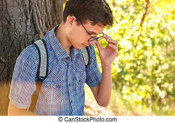 portrait of a boy in glasses nerd on a tree background