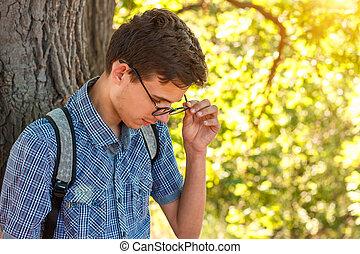 portrait of a boy in glasses nerd on a tree background