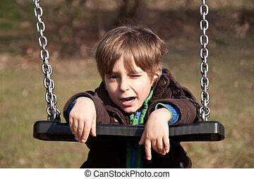 Portrait of a boy on a swing