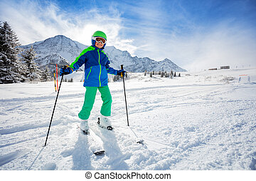Portrait of a boy stand in snow with ski on slope