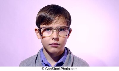 Portrait of a boy teenager schoolboy nerd glasses on purple background education