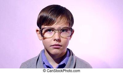 Portrait of a boy teenager schoolboy nerd glasses on purple ...