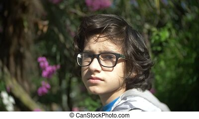 Portrait of a boy wearing glasses, looking at the camera in a summer park. 4k. slow motion