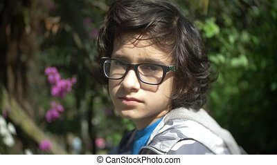 Portrait of a boy wearing glasses, looking at the camera in a summer park. slow motion