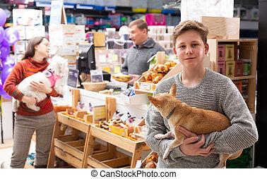 Portrait of a boy with dog in petshop
