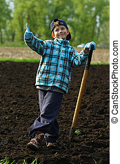 Portrait of a boy working and posing with a spade on the vegetable garden