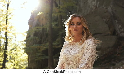 Portrait of a bride in wedding dress in a sunny park