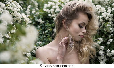 Portrait of a bride in wedding dress with flowers in a sunny park.