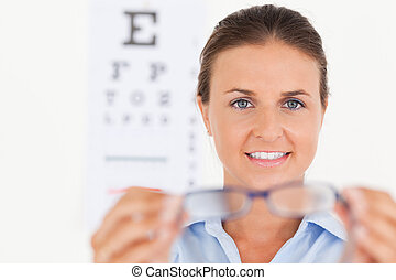 Portrait of a brunette eye specialist handing out glasses looking into the camera in her surgery