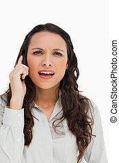 Portrait of a brunette grimacing while phoning