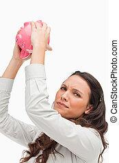 Portrait of a brunette holding an empty piggy bank