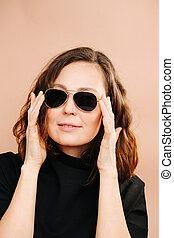 Portrait of a brunette in dark glasses on a beige background
