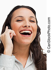 Portrait of a brunette laughing while calling