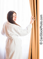 Portrait of a brunette near the window in bathrobe
