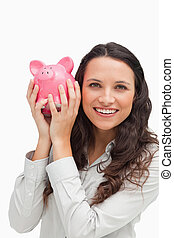 Portrait of a brunette shaking a piggy bank