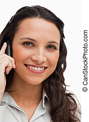 Portrait of a brunette smiling while calling