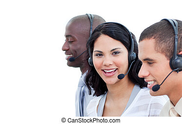 Portrait of a brunette woman and her team working in a call center against a white background
