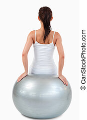 Portrait of a brunette woman working out with a ball against...